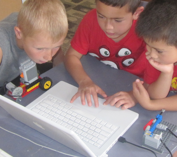 builders working on computer to program their WeDo model